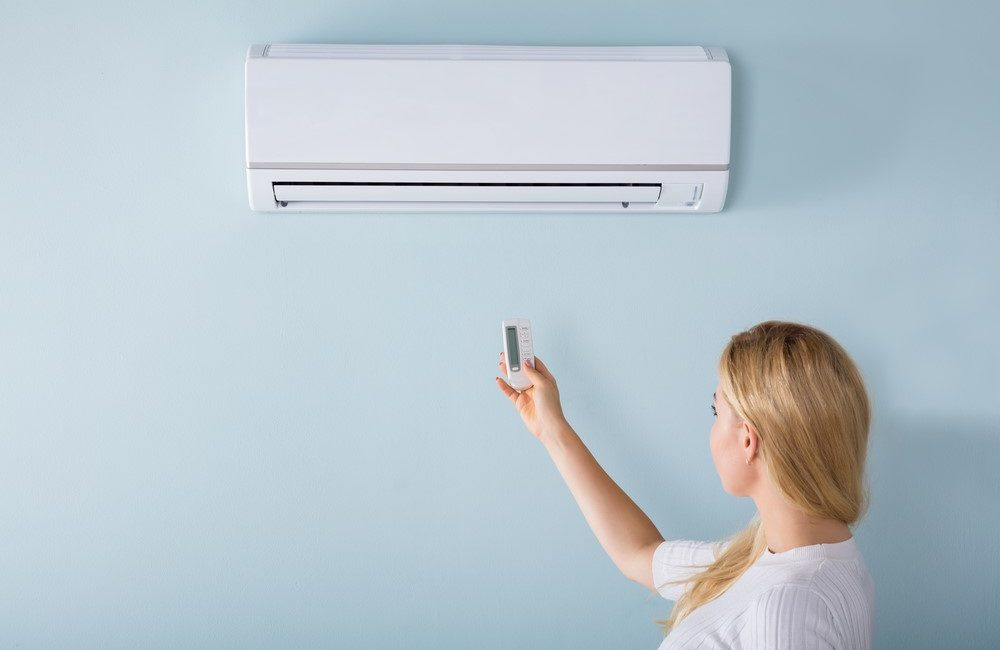 A woman lights a wall air conditioner