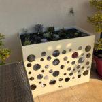 cache-clim-avec-plantes-dessus-et-motif-rond-front